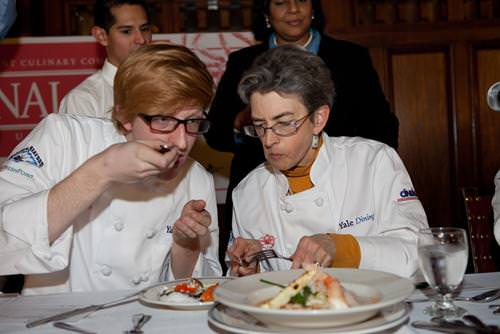 "Judges Kevin Adkisson (one of last year's winners) and Dean Mary Miller sampling dishes prepared by students, featuring wild-caught Alaskan king crab, at the Yale ""Final Cut"" cooking competition"