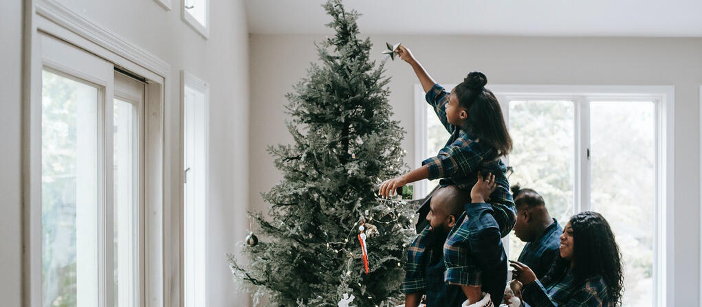 family putting a star on top of a christmas tree