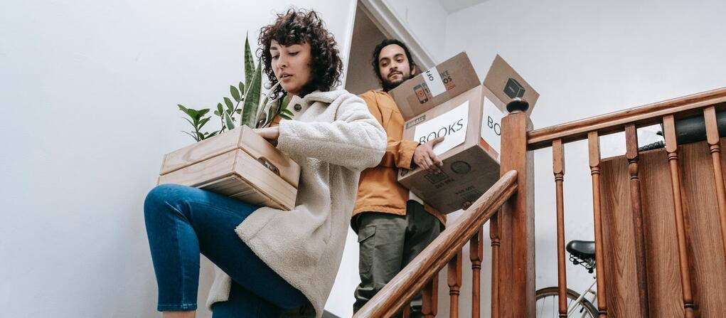 a couple carrying boxes downstairs