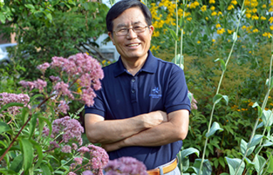 Kunso Kim standing in Marsh Botanical Garden smiling