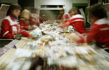 Workers at a recycling center sort through waste moving down a conveyer belt.