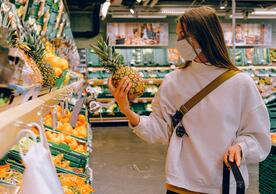 woman at the grocry store looking at a pineapple