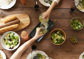 food on a thanksgiving table with people reaching for it