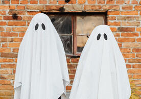 kids in ghost costumes against a brick wall